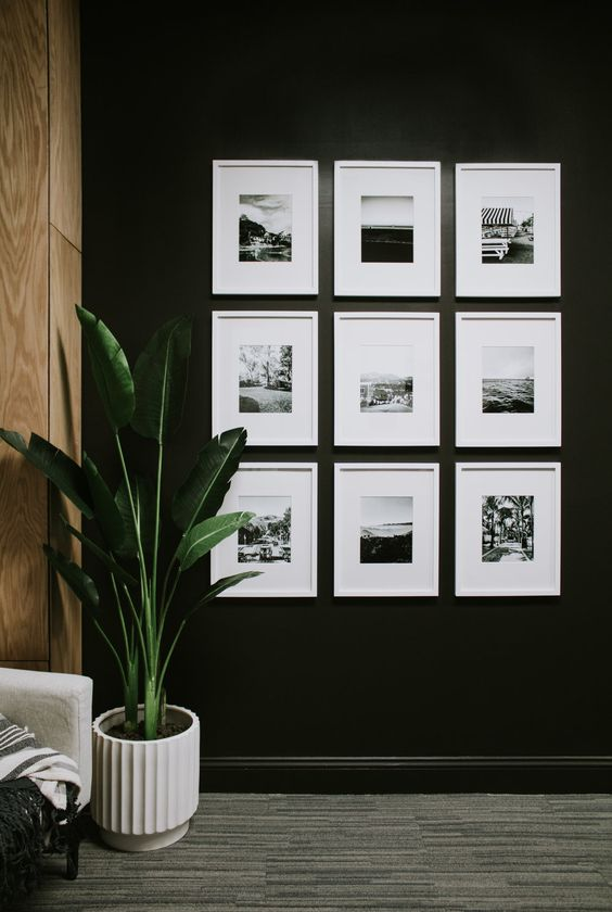 a simple symmetrical gallery wall with black and white prints in matching white frames is a cool and chic idea