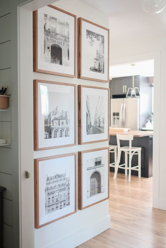a small and chic gallery wall with blonde wood frames, white matting and beautiful place photos looks a bit farmhouse