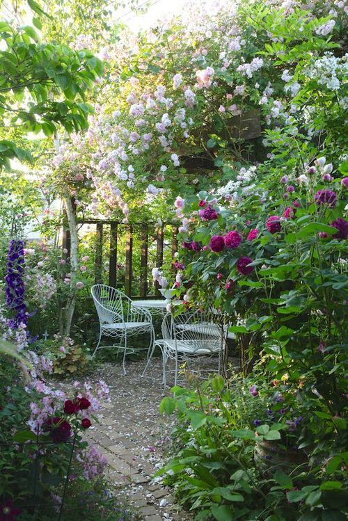 a small and chic garden dining space under blooming bushes, with refined forged garden furniture is cool