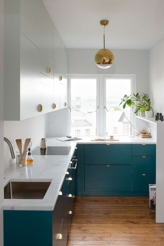 a small and chic tow-tone kitchen with gold handles and a gold pendant lamp plus potted greenery