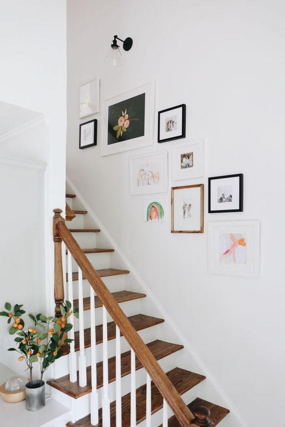 a small and cool free form gallery wall with mismatching frames and colorful artworks is a pretty idea to style the space