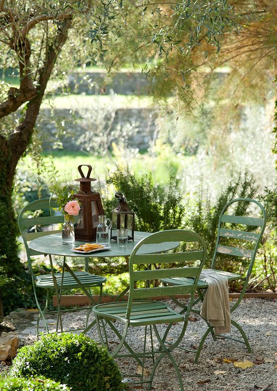 a small and cozy garden dining area wiht simple green metal furniture is located under the tree and is very inviting