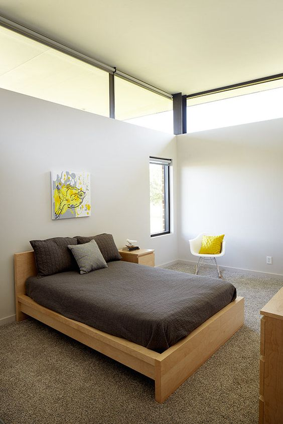 a small contemporary guest bedroom with neutral walls, blonde wood furniture, bright yellow touches and clerestory windows for more ligth here