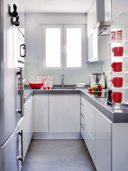 a small contemporary white kitchen with grey countertops and red tableware is a lovely space to be and is cozy