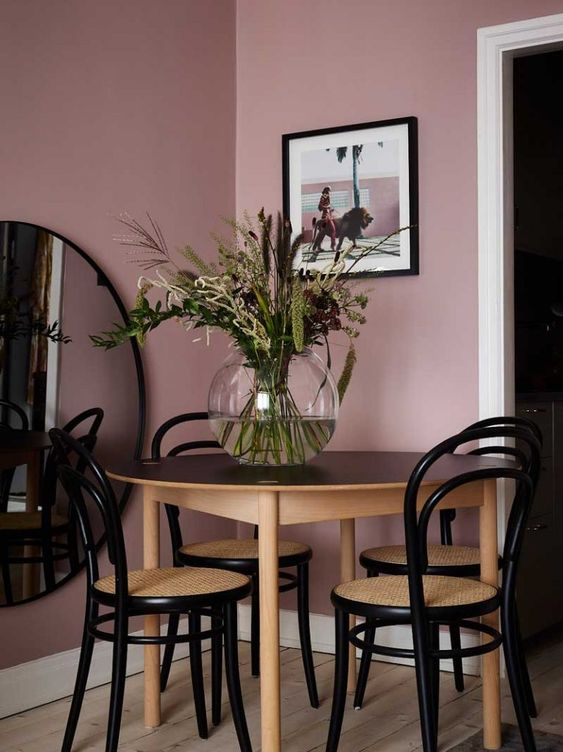 a small dining space with mauve walls, a chic table and elegant vintage chairs plus a large round mirror