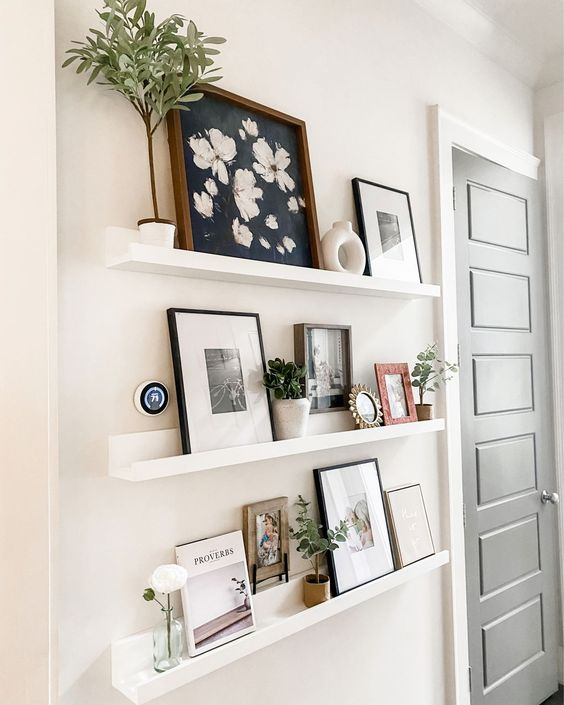 a small farmhouse gallery wall with white ledges, pretty artworks, potted greenery, vases and a photo is a chic idea