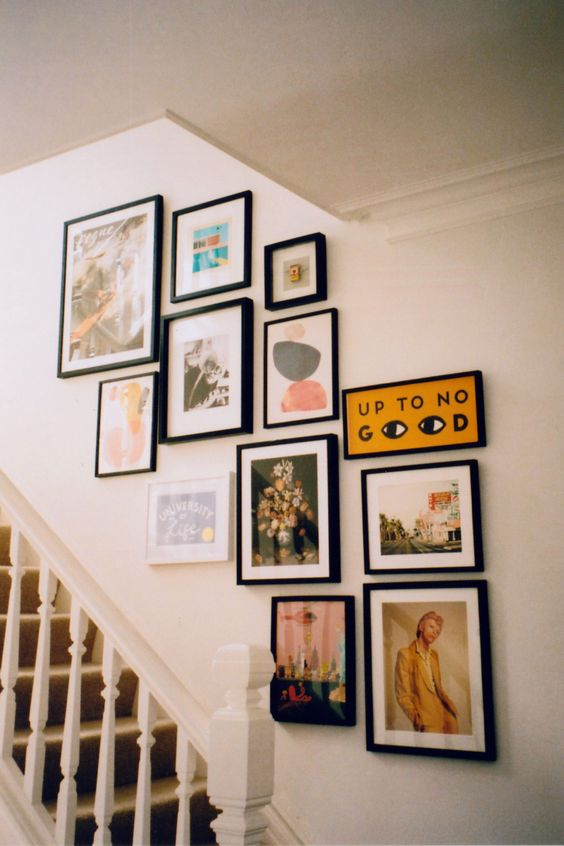a small gallery wall with mismatching black frames and pretty and bright artworks and other stuff is a cool idea to take the space over the stairs