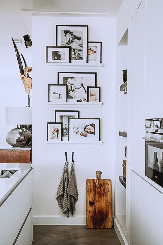 a small gallery wlal with narrow ledges in an awkward kitchen nook, with family photos on black frames is amazing