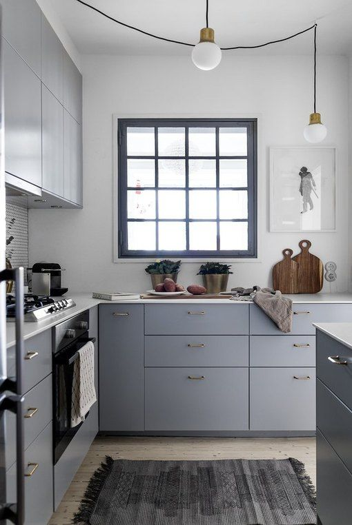 a small grey L-shaped kitchen with white countertops, a black framed window and pendant bulbs