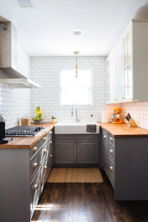 a small grey farmhouse kitchen with butcherblock countertops and white tiles on the walls is chic