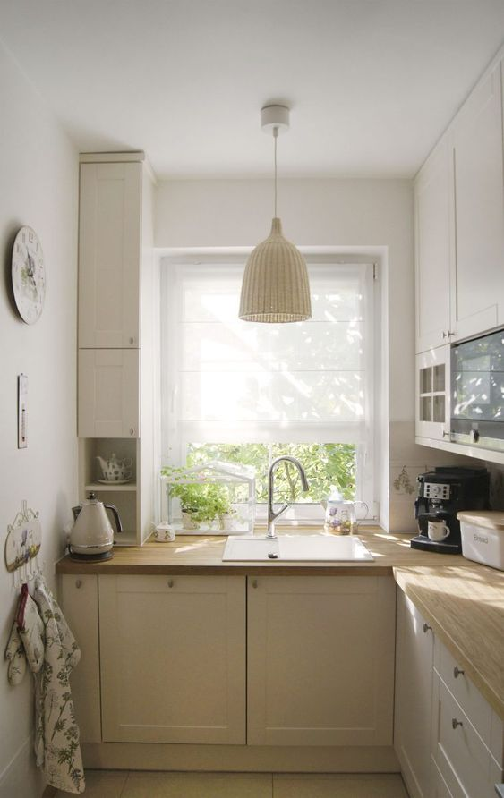 a small neutral farmhouse kitchen with light butcherblock countertops and woven lamps and natural light