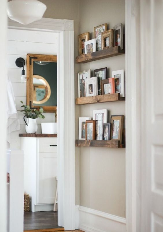 a small rustic gallery wall with stained wooden ledges and pics and artworks in wooden and colorful frames adds coziness to the space