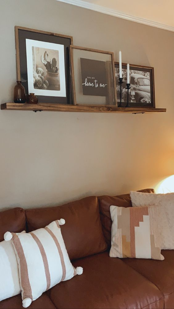 a small rustic ledge with some black and white artworks in matching wooden frames, apothecary bottles and candles