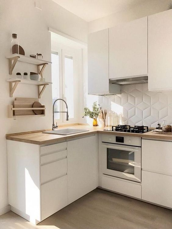 a small white L-shaped kitchen with a geometric tile backsplash and open shelves is a lovely and airy space