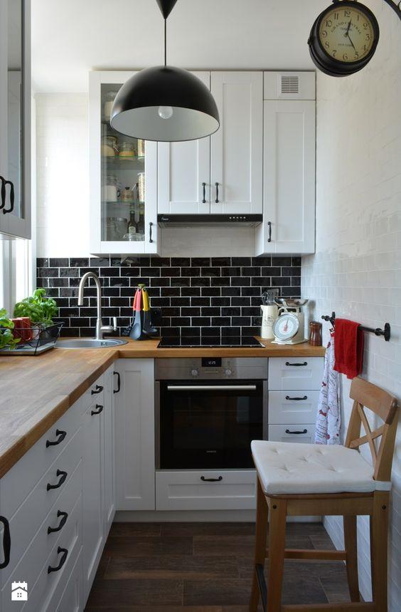 a small white L-shaped kitchen with butcherblock countertops and a black tile backsplash plus a black pendant lamp