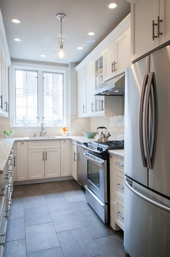 a small white U-shaped kitchen with a white tile backsplash and white countertops is a very welcoming space