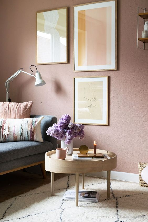 a soothing living room with a mauve accent wall, a neutral and pastel gallery wall and accessories plus a lovely wooden table
