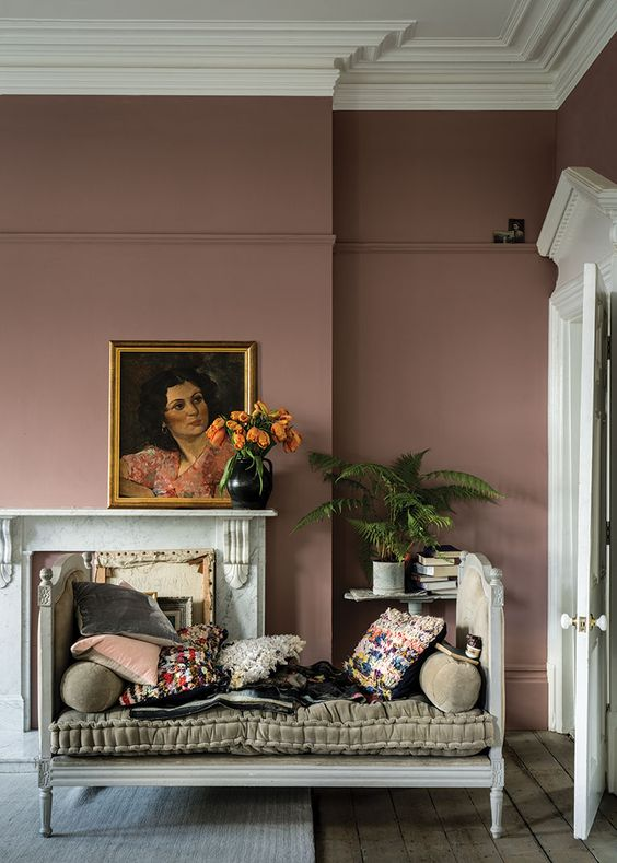 a sophisticated mauve living room with a non-working fireplace, a cool daybed and bright pillows, potted plants and a gorgeous artwork