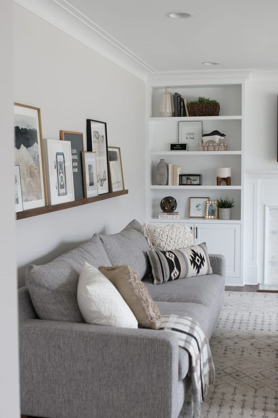 a stained ledge over the couch shows off black and white and colorful art in stained wood and black frames
