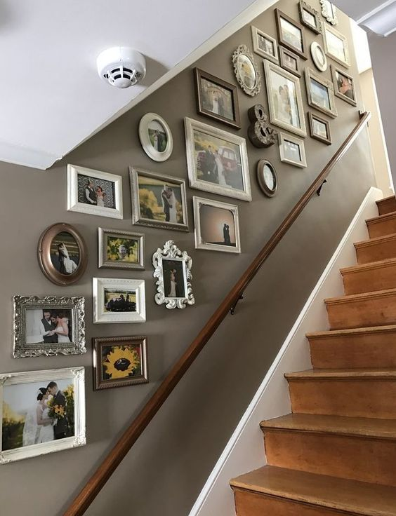 a stairway gallery wall with mismatching vintage frames and various family pics is a stylish way to style the space