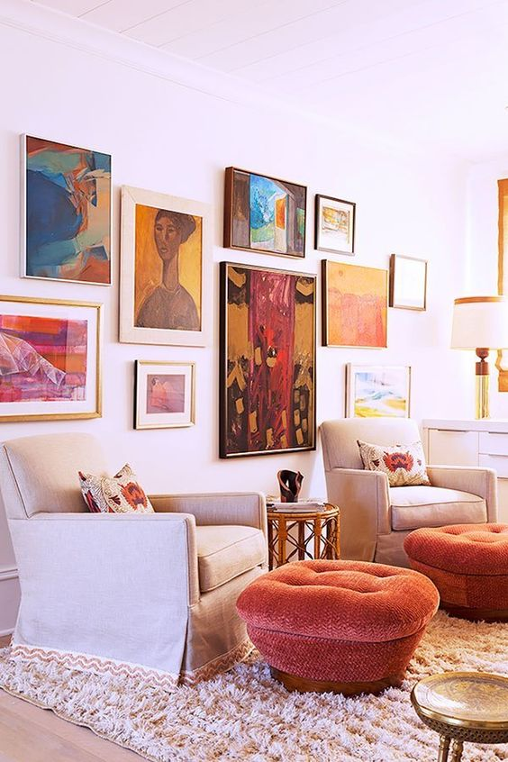a statement and colorful gallery wall with large scale and bold artworks in mismatching frames is a lovely idea