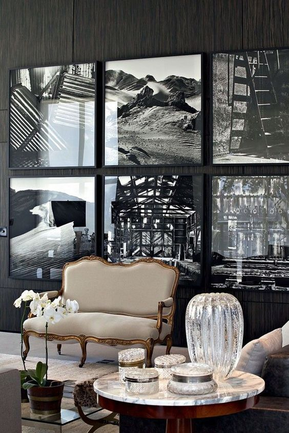 a statement gallery wall with thin black frames that seem invisible due to using black and white art and no matting