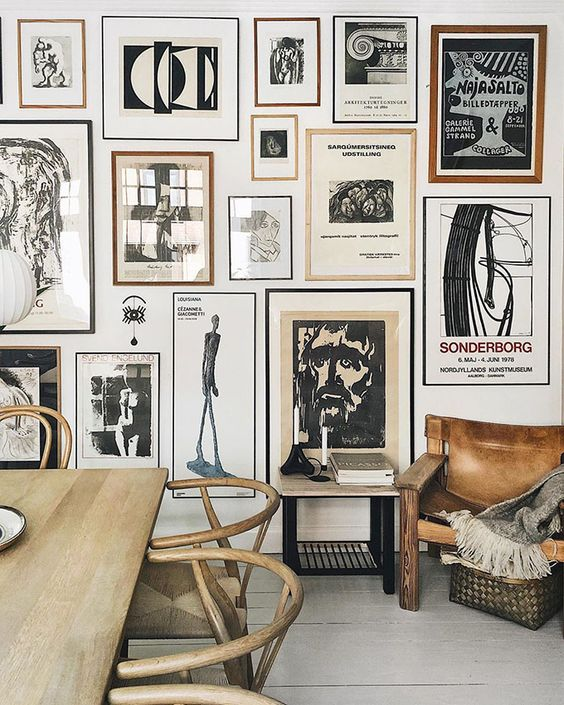a stunning gallery wall with thin black and brown frames and black and white artworks is a bold eye-catcher