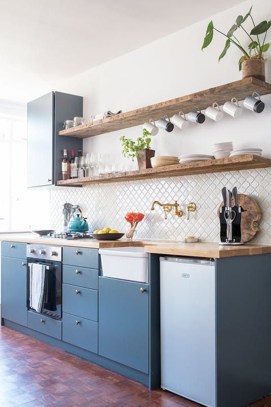 a cozy blue kitchen design with a white wall