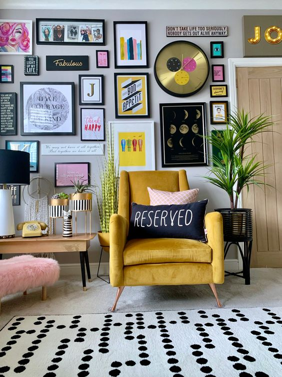 a stylish colorful gallery wall with matching black frames, colorful artworks and posters, a glam clock and bold prints