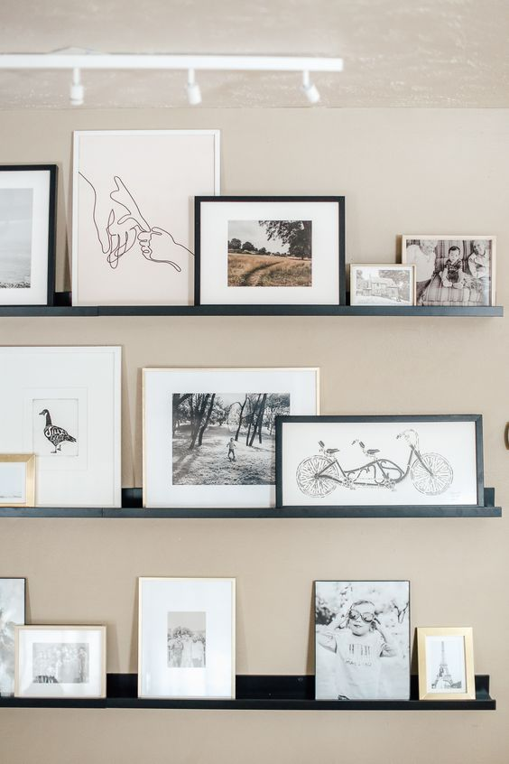 a stylish contemporary gallery wall with black ledges, black and white artworks in blonde wood, white and black frames