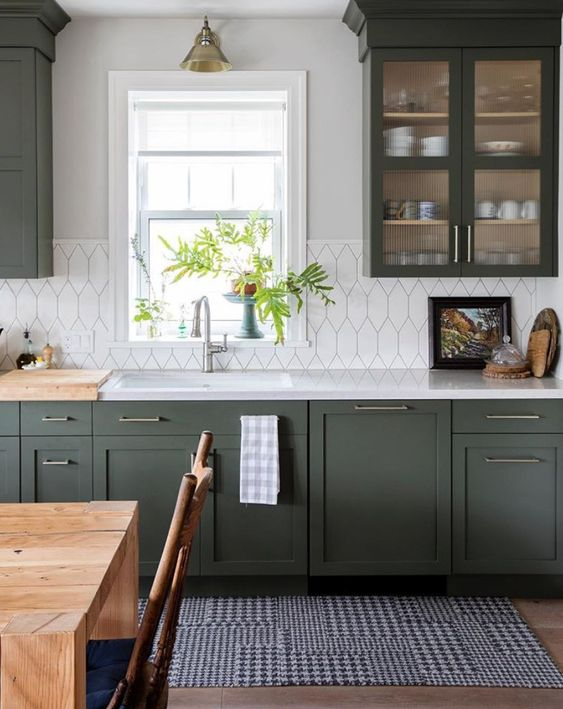 a stylish dark green kitchen with shaker cabinets, white countertops and a white tile backsplash plus retro lamps