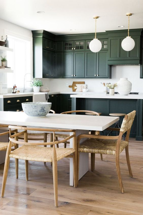 a stylish dark green kitchen with shaker cabinets, white quartz countertops and a backsplash plus pendant lamps on chain