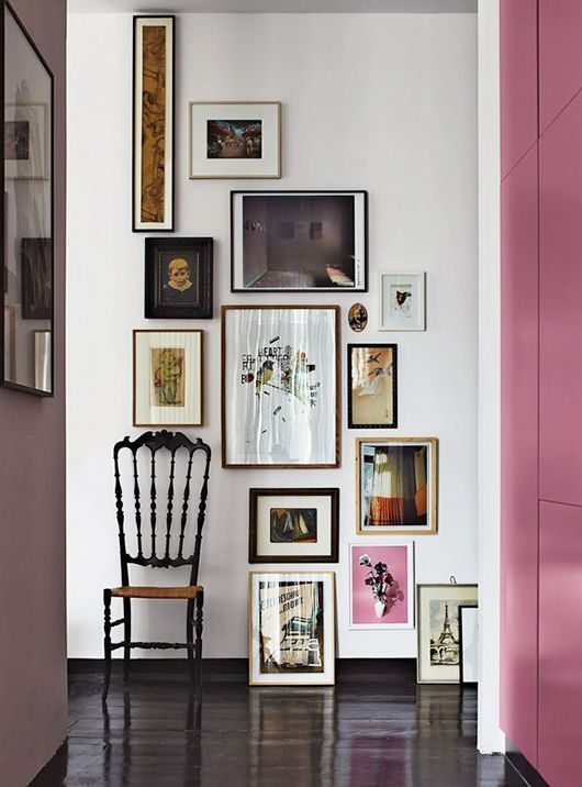 a stylish descending free form gallery wall starting with a long and narrow piece and going to the floor, with mismatching frames