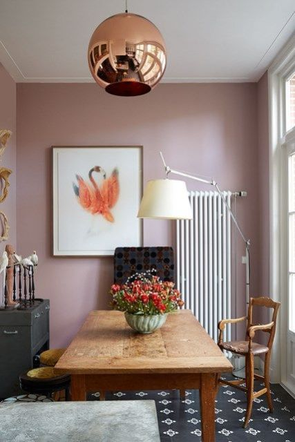 a stylish dining room with mauve walls, a copper lamp, a wooden table and vintage chairs, a dark chest, a bold artwork
