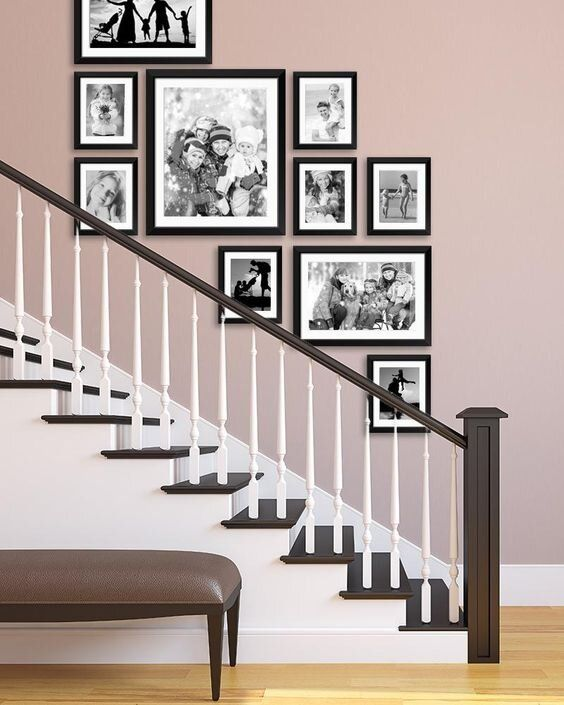 a stylish free-form gallery wall with black and white family pics and black frames adds a refined touch to the space