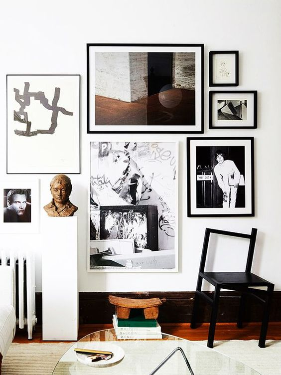 a stylish free form gallery wall with black and white frames and built around a central painting is a chic idea