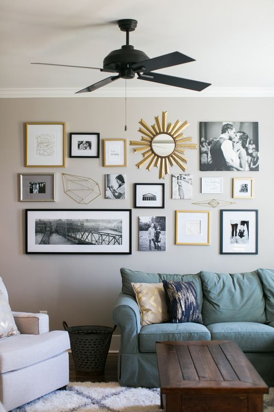 a stylish free form gallery wall with black, blonde wood and gold frames, with family photos and other prints and a mirror