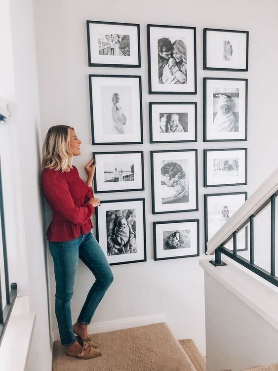 a stylish gallery wall with black and white ffamily pics in matching black frames is amazing and looks perfect