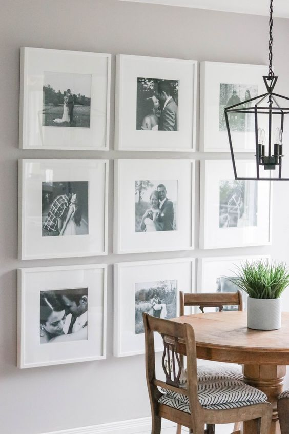 a stylish gallery wall with black and white photos in matching white frames is a preppy idea with chic