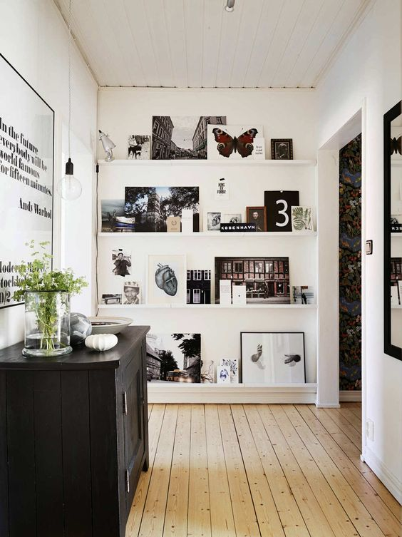 a stylish gallery wall with ledges, black and white and colorful artworks, botanical posters and a lamp is very cool