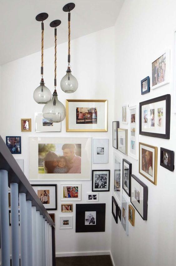 a stylish gallery wall with mismatching photos, frames of various sizes and colors is a very cool idea