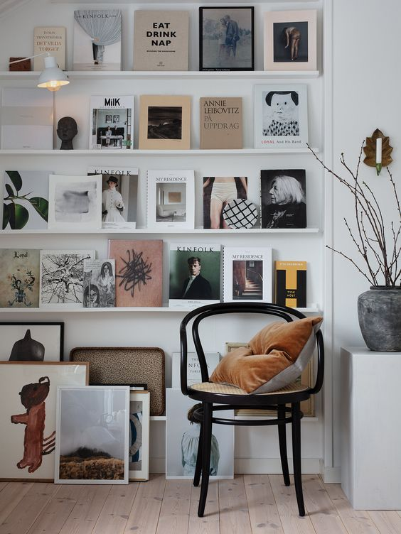a stylish gallery wall with multiple white ledges, various magazines, books and artworks plus a lamp that accents it