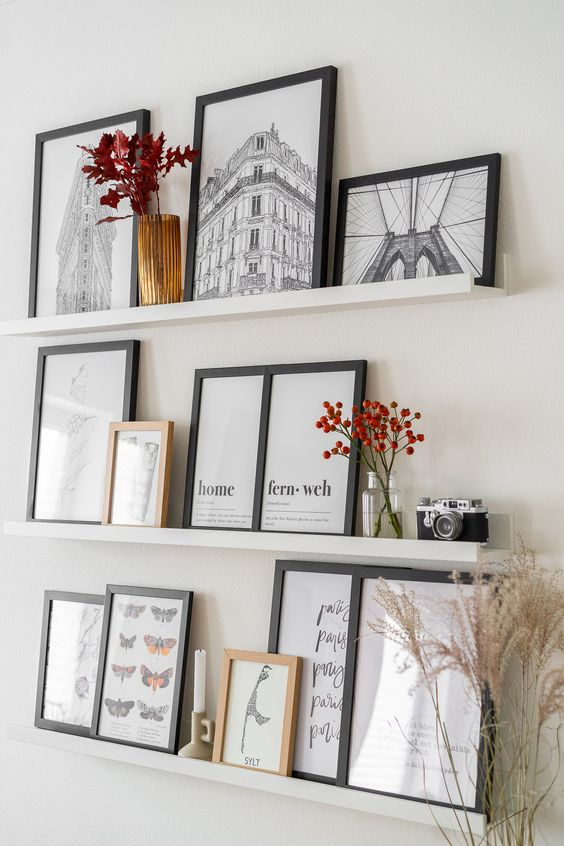 a stylish gallery wall with white ledges, art in black frames, dried blooms in vases, a candle and a vintage camera is a cool idea for a Scandi space