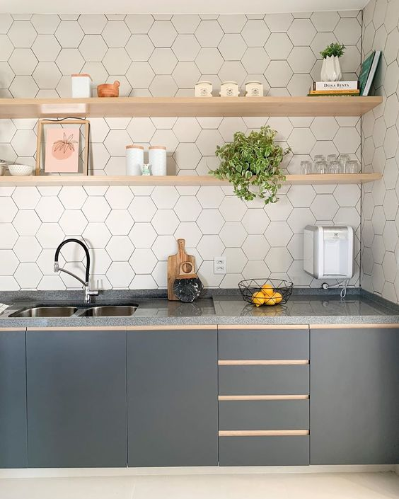 a stylish graphite grey one wall kitchen with a white hex tile backsplash and open blonde wood shelves