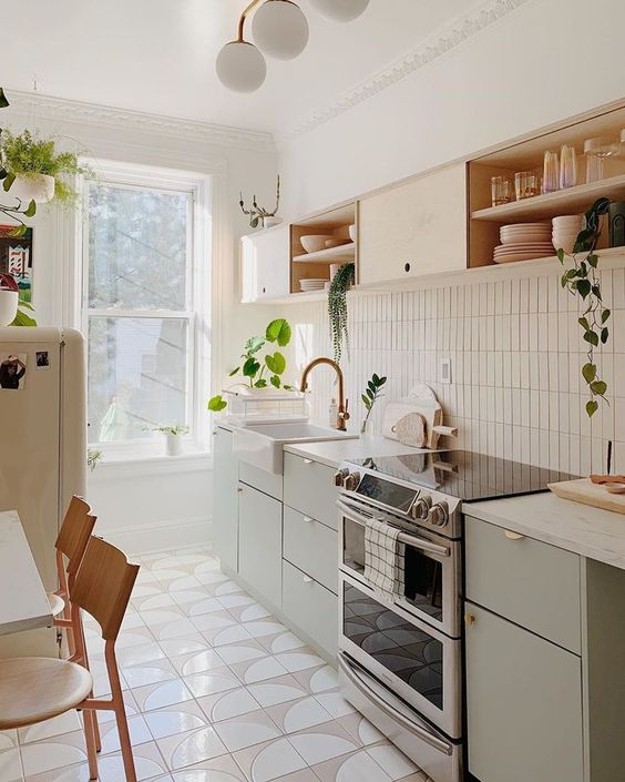 a stylish mid century modern kitchen with olive green and blonde wood cabinetry, with a skinny tile backsplash and white countertops