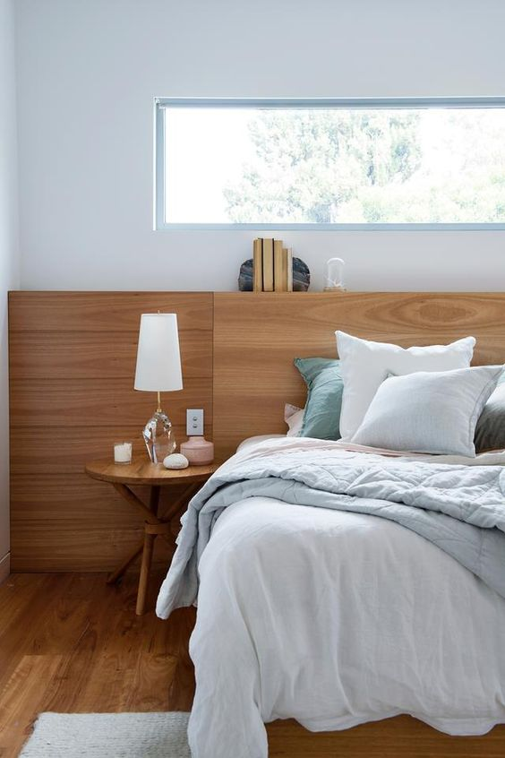 a stylish modern bedroom with much wood, a comfy bed with blue bedding, a round table and a clerestory window for privacy