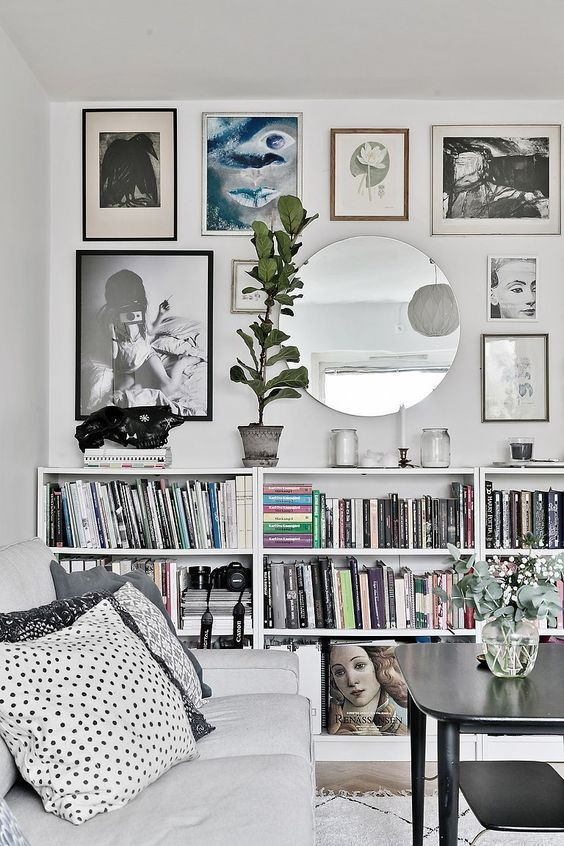 a stylish modern gallery wall with black, brown and silver frames and various types of art plus a mirror
