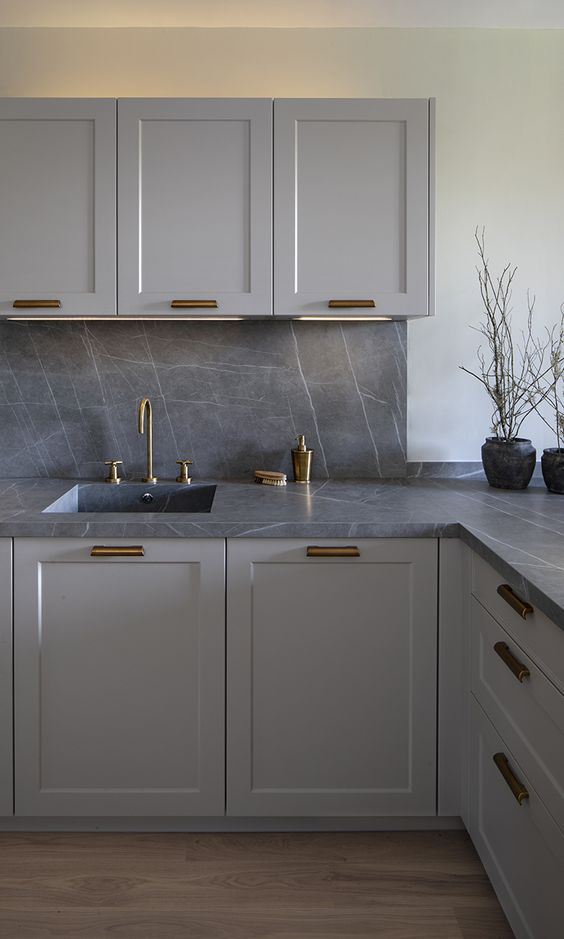 a stylish monochromatic grey kitchen with shaker style cabinets, a grey marble backsplash and countertops plus brass fixtures and handles