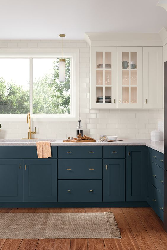 a stylish navy and white one wall kitchen with a white subway tile backsplash and countertops, a simple rug and elegant lamps