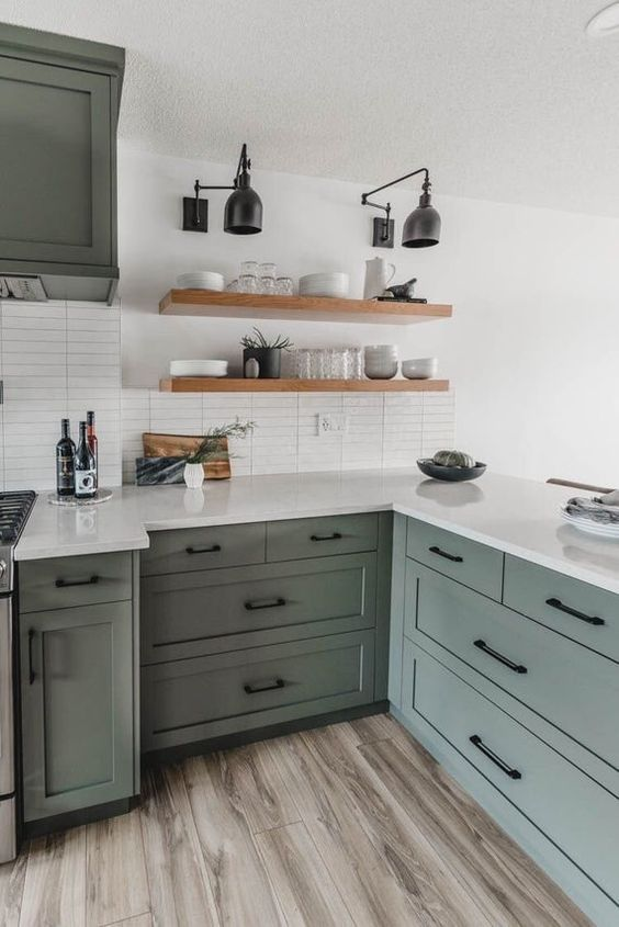 a stylish sage green kitchen with shaker style cabinets, white countertops and a white skinny tile backsplash plus floating shelves